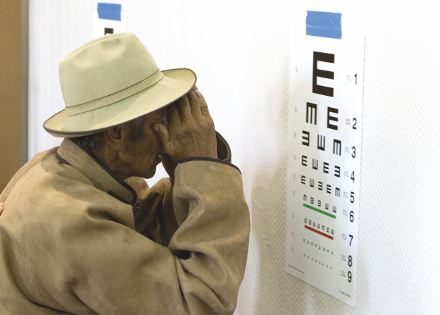 A Mongolian man in a brown coat and tan hat standing close to an eye chart, checking his eyesight prior to his cataract surgery.