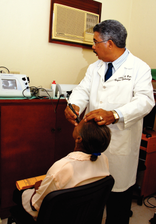 A male doctor in the Dominican Republic, wearing a long white coat, using a long metal device to check the eyesight of a woman sitting down.