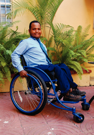 A man from the Dominican Republic, wearing blue pants, a blue shirt, and a blue tie, sitting and smiling in a new, shiny blue wheelchair.