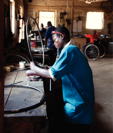 An African man in a blue shirt standing beside a table in a wheelchair workshop, repairing a round black wheelchair part with other men nearby.