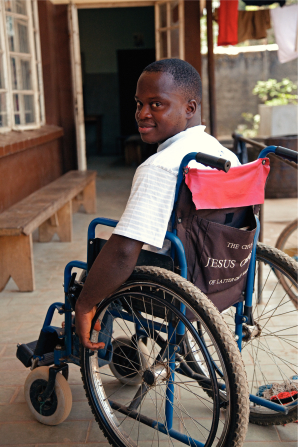 A man from Africa in a light blue striped shirt, smiling and sitting outside in a wheelchair, resting his hand on a wheel.