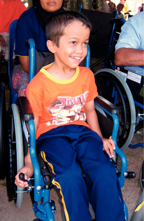A young boy from Thailand in blue sweatpants and an orange shirt, smiling and sitting in a blue wheelchair.
