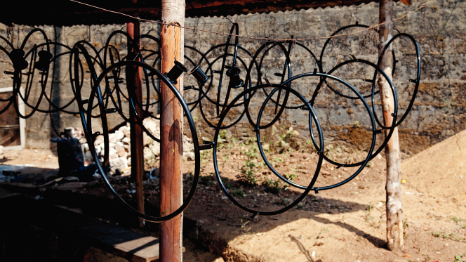 Many round black wheelchair parts hanging down from a horizontal string in Africa.
