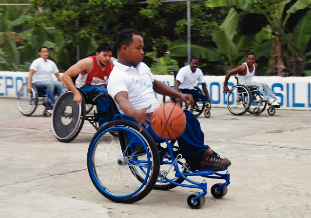 In the Dominican Republic, a man in a wheelchair bounces a basketball with four men and one woman in wheelchairs on a basketball court.