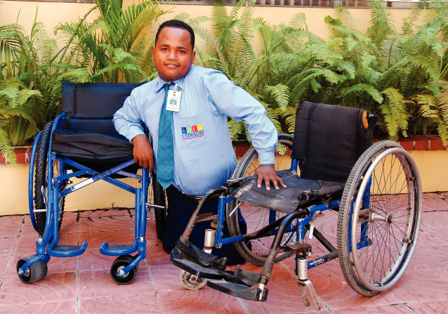A man from the Dominican Republic balancing himself between a rusting, torn, dirty wheelchair and a new, shiny black and blue wheelchair.
