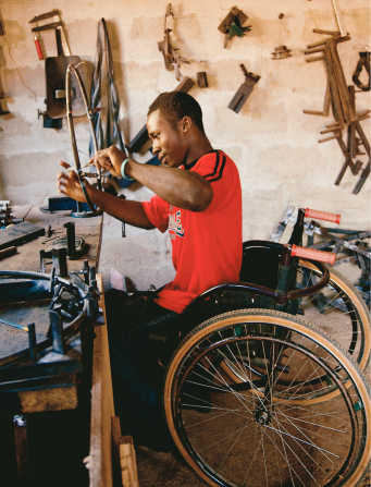 A man from Africa in a bright red shirt, sitting in a wheelchair and repairing a round wheel piece from another wheelchair.