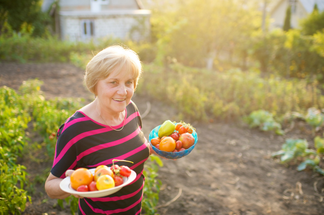 A woman stands in a garden in the evening holding two bowls full of fresh peppers and tomatoes.