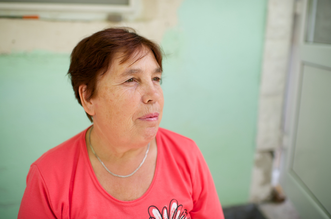 A woman with short dark hair and a pink T-shirt sits near a green wall in Romania.