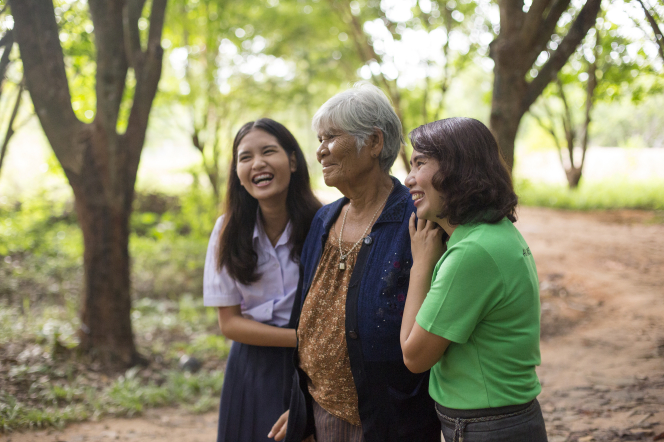 Three women of different ages walk together on a path through a grove of green trees.