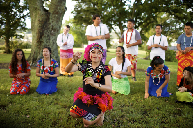 A group of young men and young women in New Zealand dress up in colorful traditional clothing and dance outside.