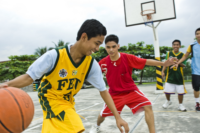 Young men in jerseys of various colors play basketball on an outdoor court.