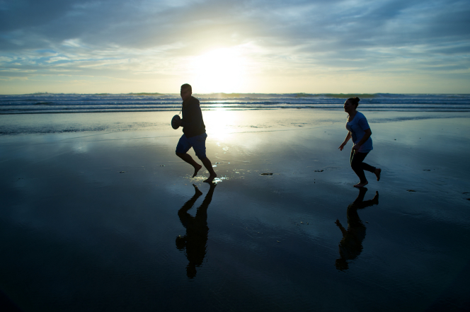 A young man runs through water on the beach carrying a football, with a young woman chasing him as the sun sets.