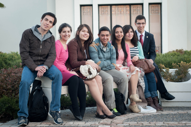 A group of youth sit on a bench by green bushes outside the Santiago Chile Temple.