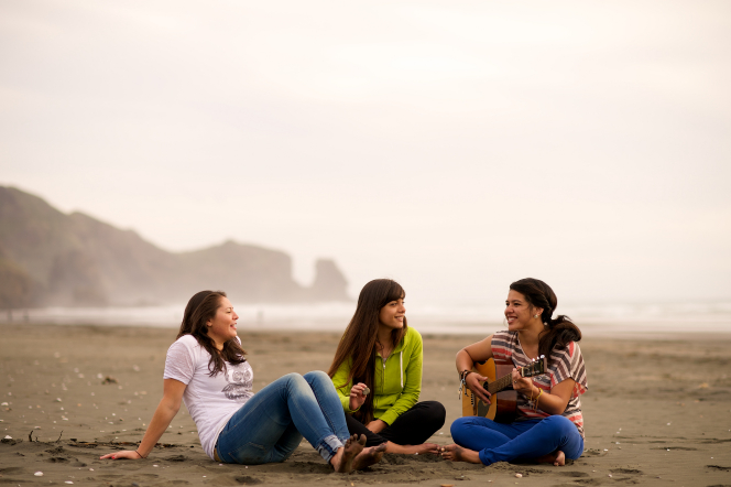 A young woman plays her guitar on the beach while two other young women sit on the sand with her, with water and mountains in the background.