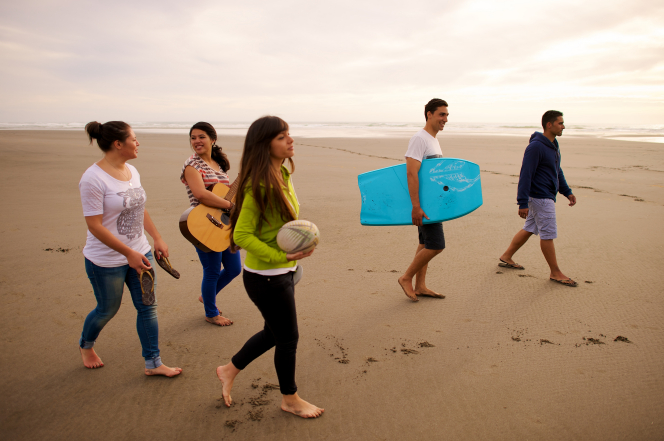 A group of youth on the beach, with one young woman carrying a ball, another carrying a guitar, a young man carrying a bodyboard, and another young man and young woman walking nearby.