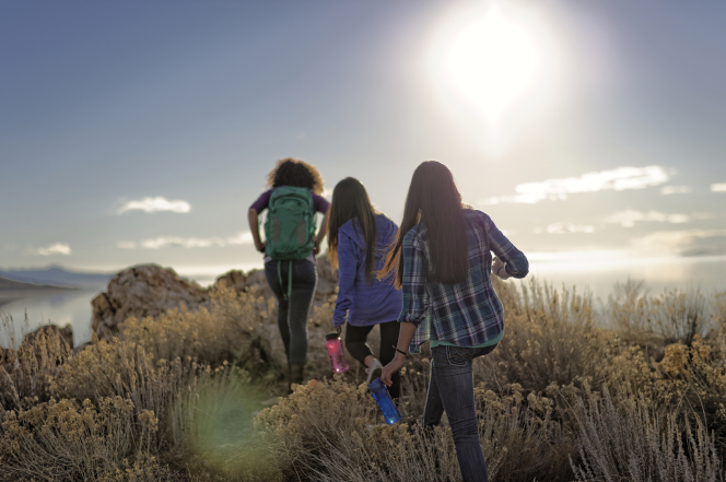 One young woman wearing a backpack and two other young women carrying water bottles hike together over a hill at girls' camp.