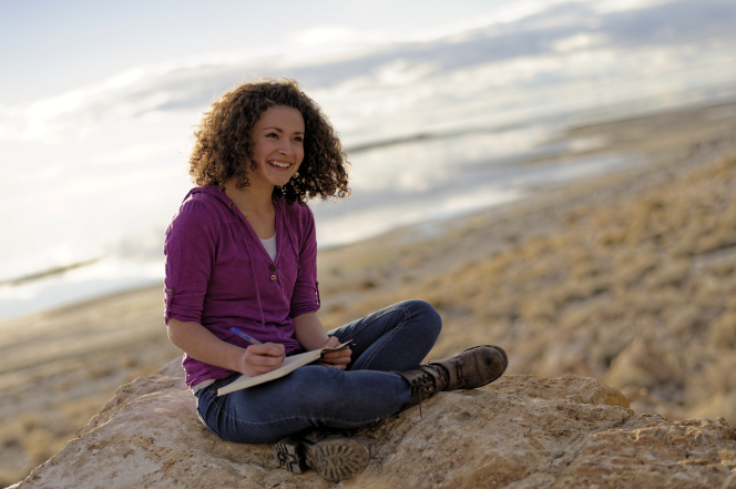 A young woman with brown curly hair, a purple shirt, jeans, and boots sits on a rock and writes in a journal.