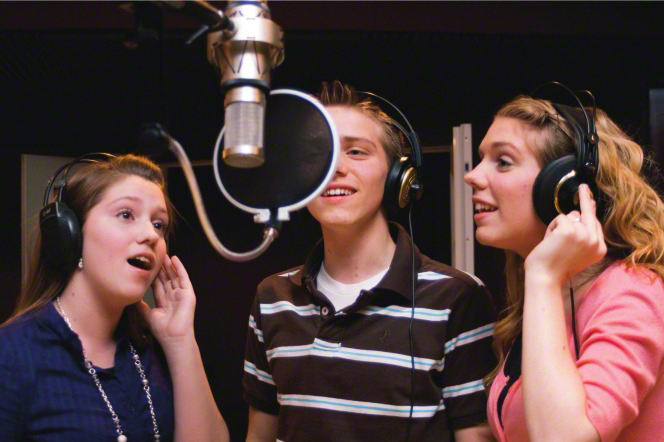 A young man and two young women wearing headphones stand around a hanging mike and sing in a recording studio.