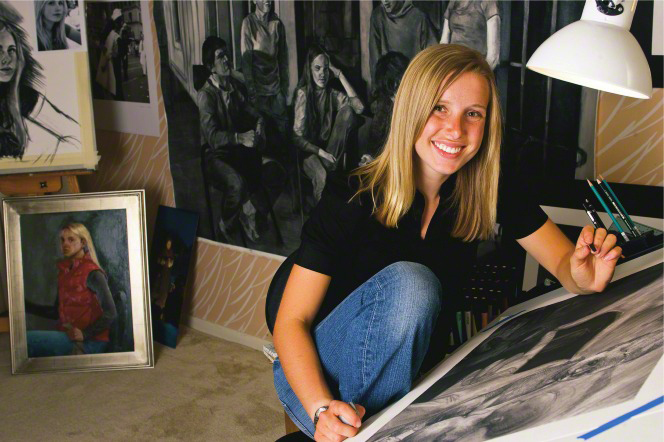 A young blonde woman in jeans and a black shirt sits in her studio and draws with charcoal.