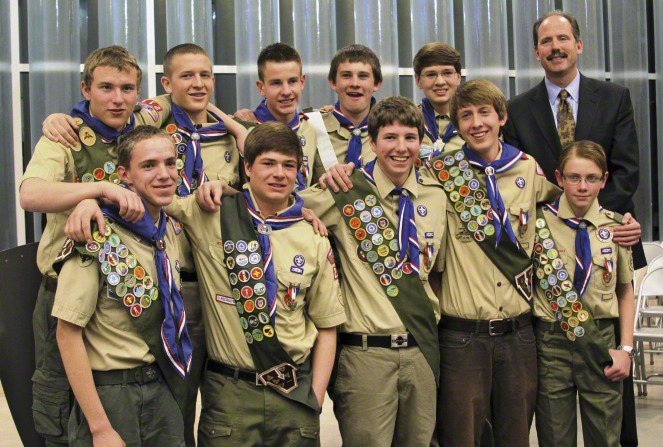A group of Boy Scouts standing in two rows with their arms resting on each other's shoulders, with their leader dressed in a suit.