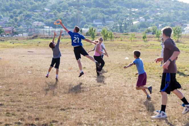 A young man jumps into the air to catch a Frisbee as a group of boys and girls run after him.