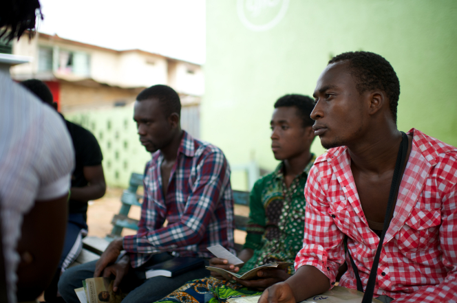 A group of young men in Africa sit on a bench together, look at pamphlets about Jesus Christ, and discuss the gospel.