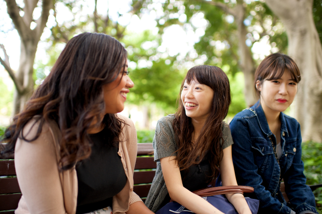 Three young women with dark brown hair sit on a wooden park bench and talk together.