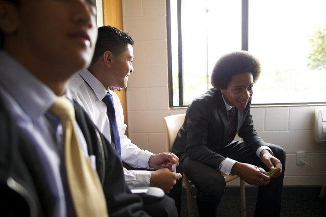 Three young men in white shirts and ties sit in chairs by a window in Sunday School.