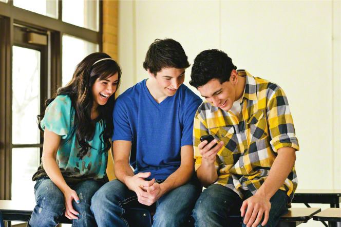 A young man holds out his phone to another young man and a young woman, who all read a text on the young man's phone and smile.
