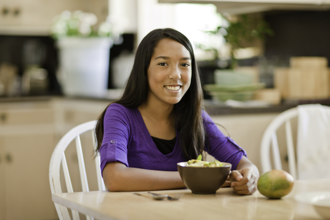 A young woman in a purple shirt sits at a kitchen table with a bowl of food and a piece of fruit in front of her.