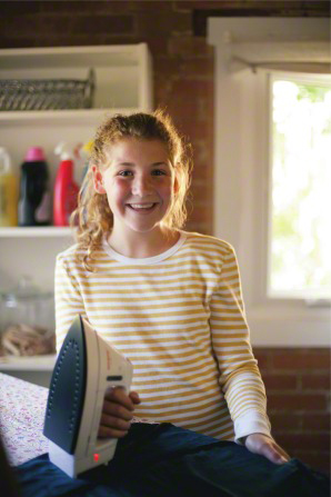 A young woman in a striped shirt smiles and stands at an ironing board while holding an iron.