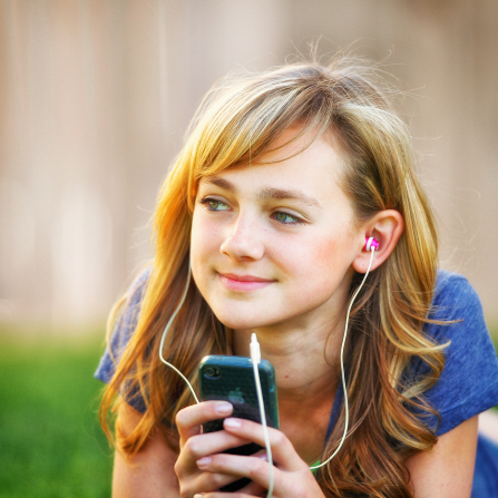 A young woman with light brown hair and a blue shirt lies on the grass, listening to music through earbuds.