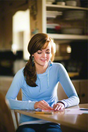 A young brown-haired woman in a light blue sweater sits down at a table and folds up a letter she has written.