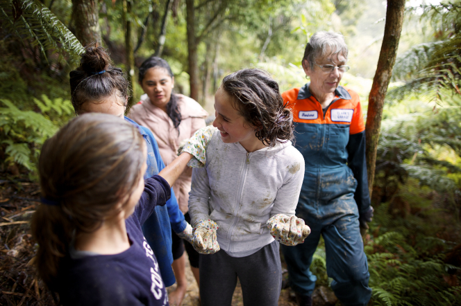 A group of young women and one leader wear work gloves while doing a service project outside together.