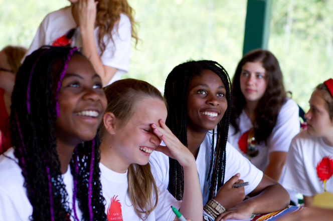 A group of girls in white T-shirts sit at a table outside and laugh during girls' camp.
