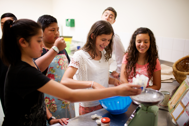 A young woman mixes ingredients in a bowl as another young woman adds to the bowl and some young men stand behind and help.