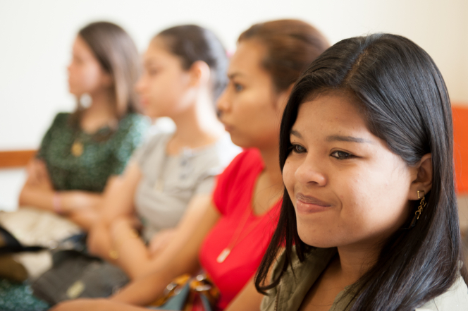 A group of young women sit in chairs in a classroom during a Sunday lesson.