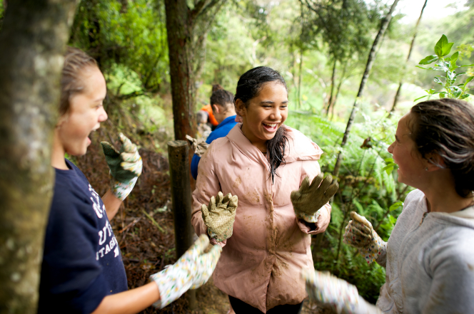 A group of young women wear work gloves while standing by trees and doing a service project together.