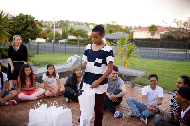 A young man stands in the middle of a circle of youth at a Mutual activity in Australia.