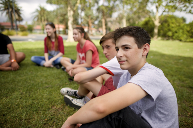 A group of young men and young women sitting on the grass outside.