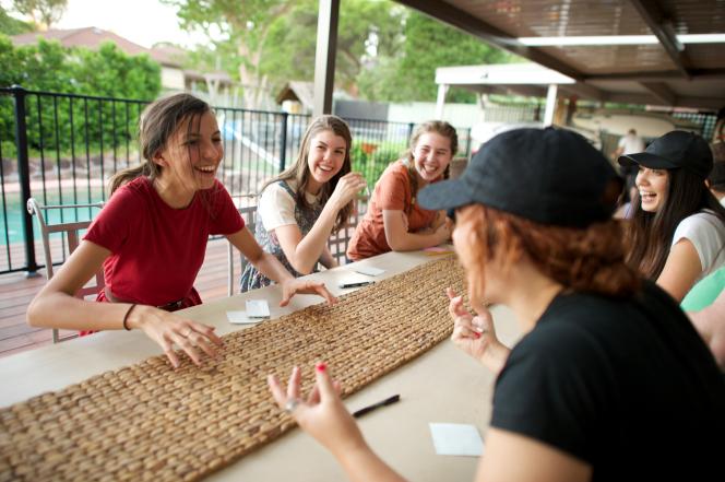 A group of young women sitting around a table outside and playing games.
