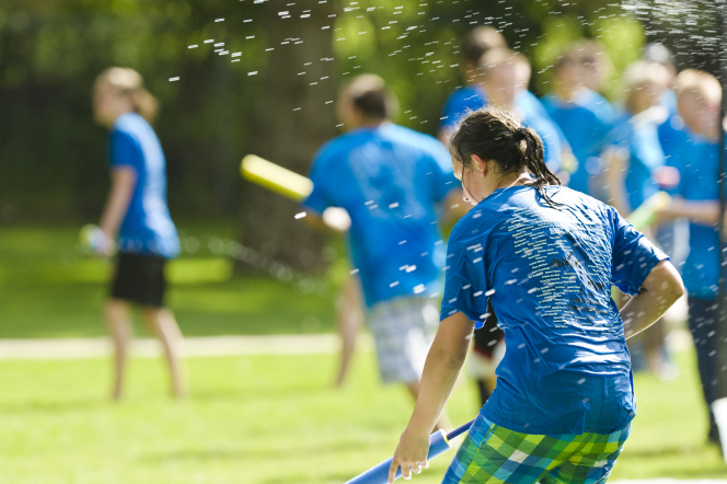 A group of youth in blue T-shirts holding water guns and playing water games outside.
