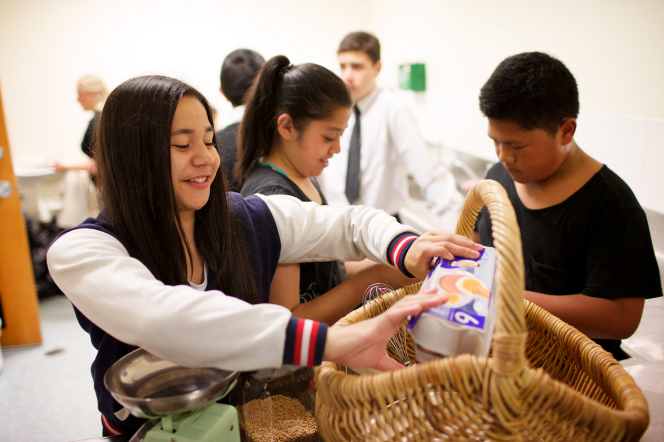 A young woman pulls a carton of eggs out of a basket while a group of young men and young women bake together in a kitchen.
