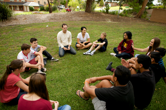 A group of youth sitting in a circle on the grass and playing a game together.