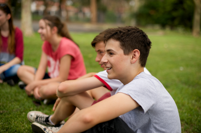 A young brown-haired man in a T-shirt sitting on the grass outside with a group of youth.