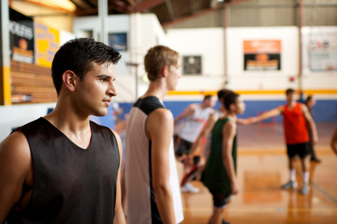 A young man in a black tank top waits on the sidelines while other young men play basketball on a court in a gym.