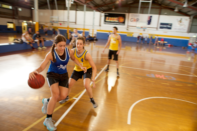 A young woman dribbles a ball down the court as another young woman tries to take it from her. Other youth are seen in the background on the basketball court.