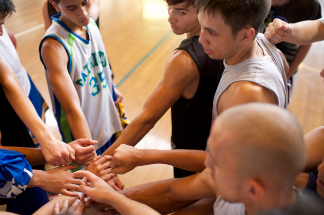 A team of young men getting ready to start a basketball game, each extending one hand to give a cheer.