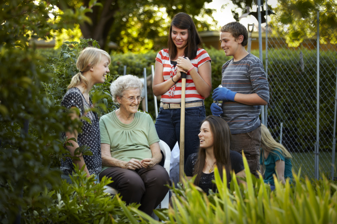 An elderly woman sits on a bench while three young women and one young man help with her garden.