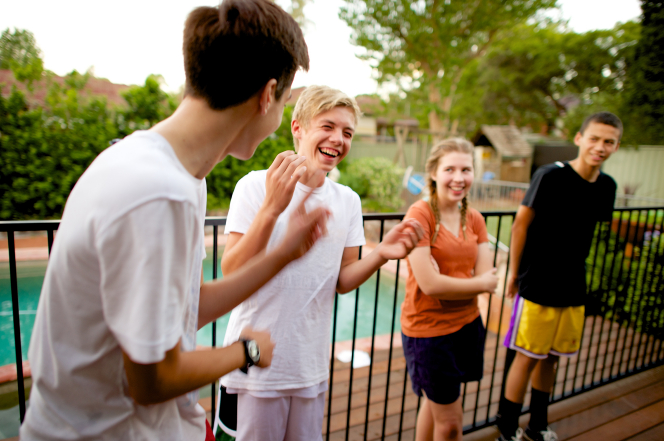 Three young men and one young woman hang out together outside and laugh.
